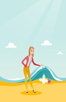 Mulher que mostra garrafas plásticas sob a onda do mar.
