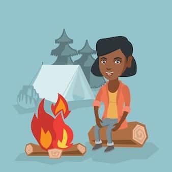 Mulher que senta-se no log perto da fogueira no acampamento.