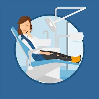 Mulher que sofre na cadeira odontológica.