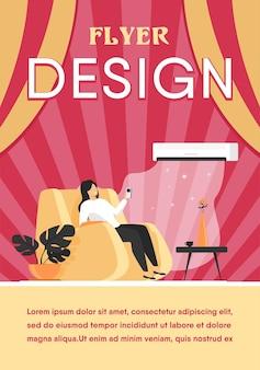 Mulher relaxando na poltrona em casa, ligando o sistema de ar condicionado, segurando um dispositivo de controle remoto