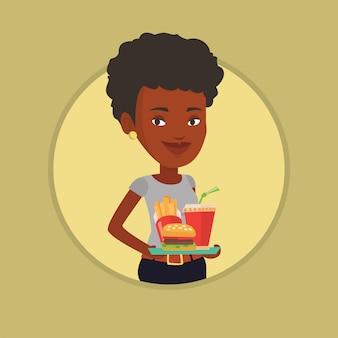 Mulher segurando a bandeja cheia de fast-food.