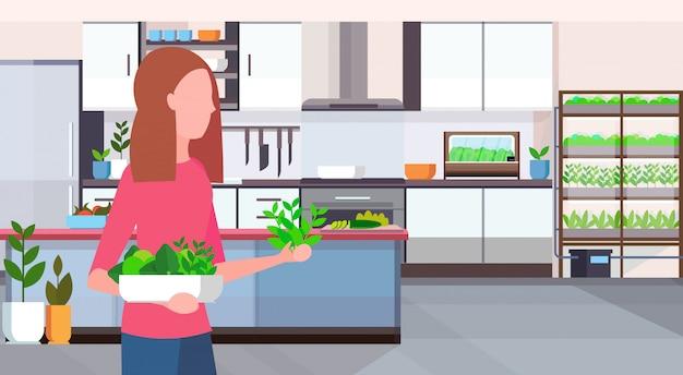 Mulher segurando diferentes salada orgânica deixa conceito de alimento saudável plantas inteligentes sistema moderno cozinha interior retrato horizontal plana