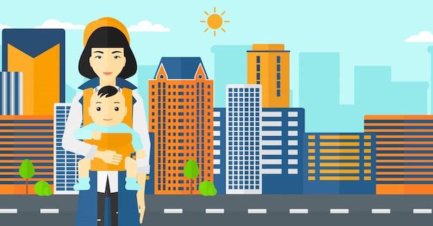 Mulher segurando o bebê no estilingue.