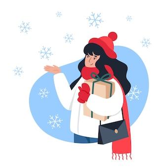 Mulher segurando um presente e pegando flocos de neve com a mão, caminhada de inverno, clima de natal
