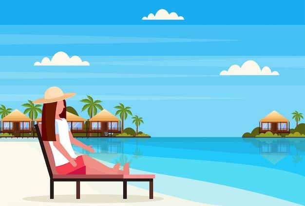 Mulher sentada espreguiçadeira espreguiçadeira na ilha tropical villa bangalô hotel praia à beira-mar verde palmas paisagem verão férias plana