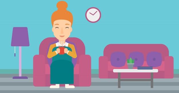 Mulher sentada na cadeira com uma xícara de chá.