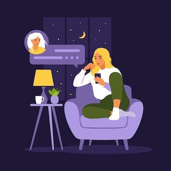 Mulher sentada no sofá com o telefone à noite.