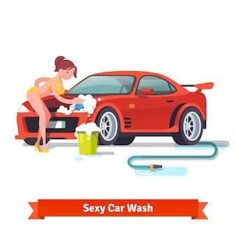 Mulher sexy no roupa de banho que lava o carro de esportes vermelho