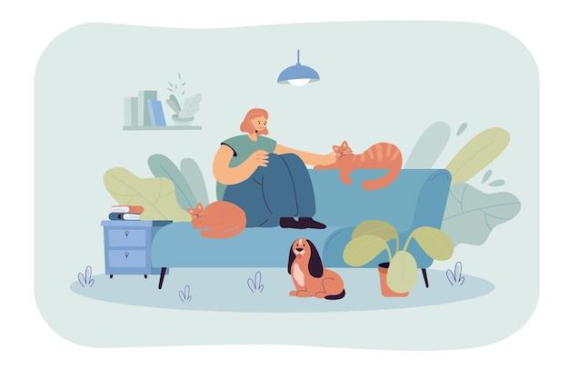 Mulher sorridente, sentada no sofá, acariciando o gato