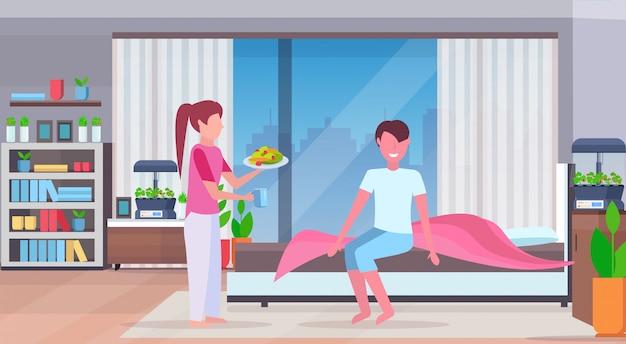 Mulher trazendo legumes frescos e café da manhã salada de frutas para o homem na cama apartamento moderno quarto interior com plantas de casa de recipiente de vidro terrário crescendo conceito plana e horizontal comprimento total