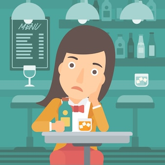Mulher triste com garrafa e copo.