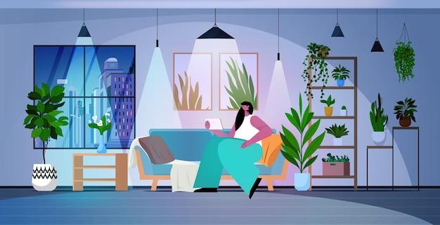 Mulher usando tablet pc na noite escura sala de estar rede de mídia social conceito de comunicação on-line horizontal ilustração vetorial de corpo inteiro