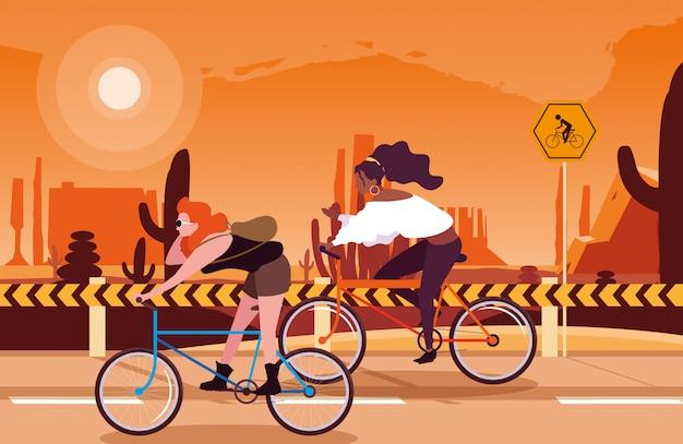 Mulheres andando de bicicleta na paisagem do deserto com sinalização para ciclista