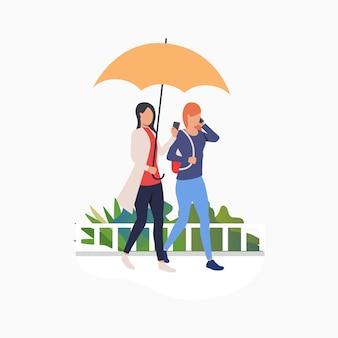 Mulheres andando sob o guarda-chuva e usando smartphones
