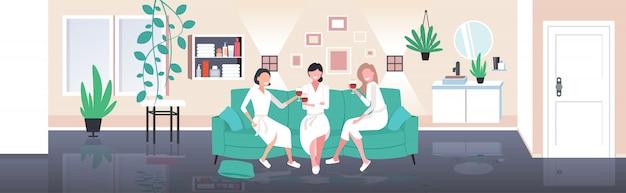 Mulheres bonitas em roupões de banho bebendo vinho se divertindo conceito de cuidados em casa meninas relaxando no sofá