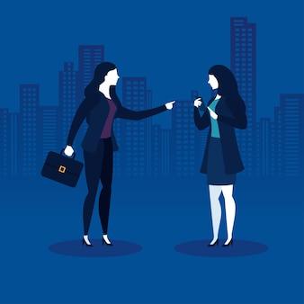 Mulheres de negócios com mala e smartphone em frente aos prédios da cidade