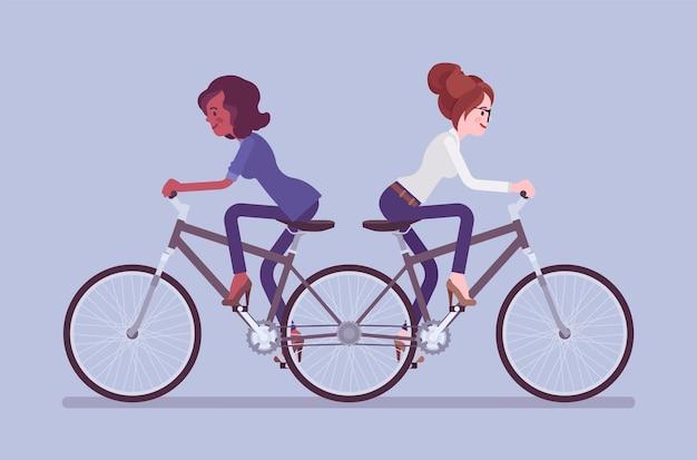 Mulheres de negócios empurra-me e puxa-te bicicleta tandem
