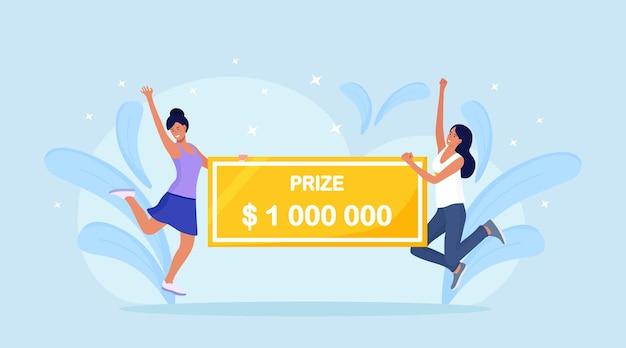 Mulheres felizes, ganhando prêmio em dinheiro. vencedores com cheque bancário de um milhão de dólares. garota de sorte ganhar o jackpot na loteria. fortuna, conceito de sorte