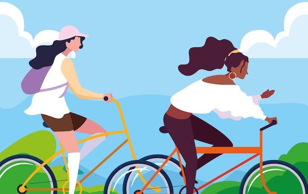 Mulheres jovens andando de bicicleta com a paisagem