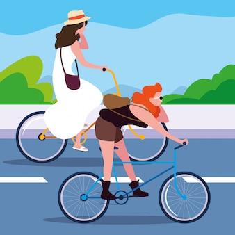 Mulheres jovens andando de bicicleta na estrada