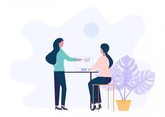 Mulheres jovens está sentado em uma mesa com computador e seu colega está apontando