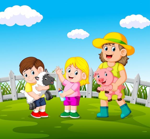 Mulheres jovens segurando o porco e crianças felizes segurando ovelhas