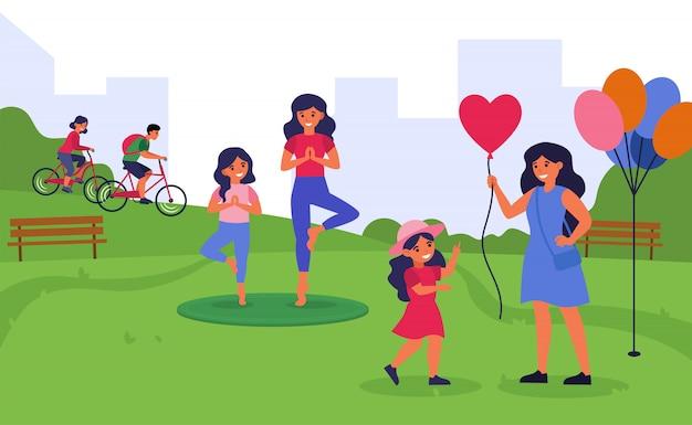 Mulheres que passam o tempo com filhas pequenas no parque público