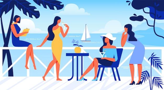 Mulheres relaxantes no terraço ao ar livre com vista para o mar.
