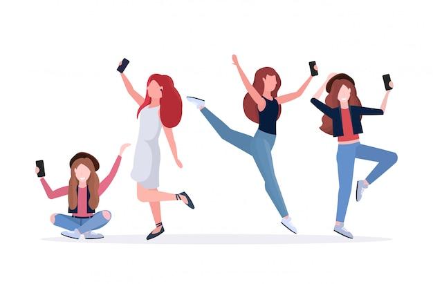 Mulheres tirando foto de selfie na câmera do smartphone personagens de desenhos animados femininos casuais fotografando em poses diferentes fundo branco comprimento total horizontal
