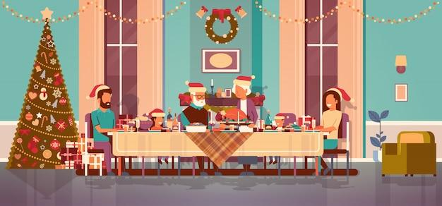Multi geração família comemorando o ano novo feriado pessoas sentadas à mesa conceito jantar tradicional decorada árvore de natal sala interior horizontal