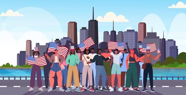 Multidão de pessoas segurando bandeiras dos eua comemorando 4 de julho, dia da independência americana