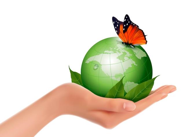 Mundo verde com folha e borboleta na mão da mulher.