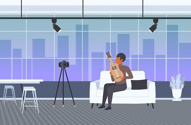 Música blogger tocando guitarra streaming musical conceito blog americano africano homem gravação de vídeo usando a câmera no tripé moderna sala de estar interior horizontal comprimento total