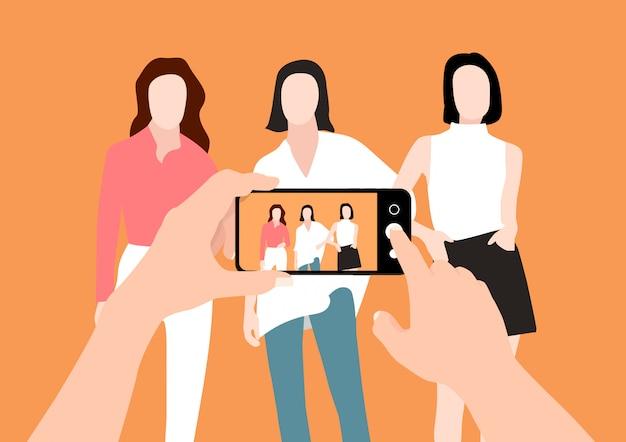 Nas mãos de um homem tirando grupo de fotos de mulher com um telefone inteligente.
