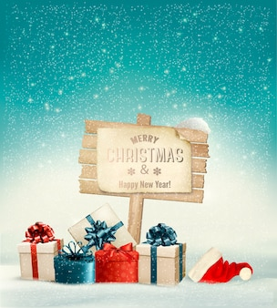 Natal de inverno com uma placa, caixas de presente e um fundo de chapéu de papai noel.