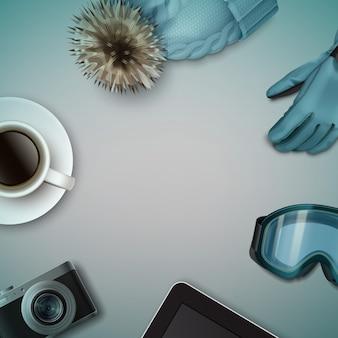 Natureza morta de inverno: boné de malha azul com pom-pom, luva, óculos de esqui, xícara de café, câmera fotográfica, tablet e vista superior do copyspace