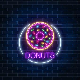 Néon brilhante sinal de donuts no quadro do círculo em uma parede de tijolos escuros