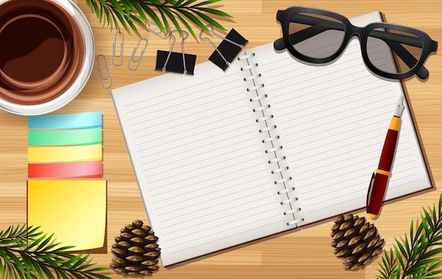 Nota em branco e óculos fecham no fundo da mesa com alguns adereços de folhas