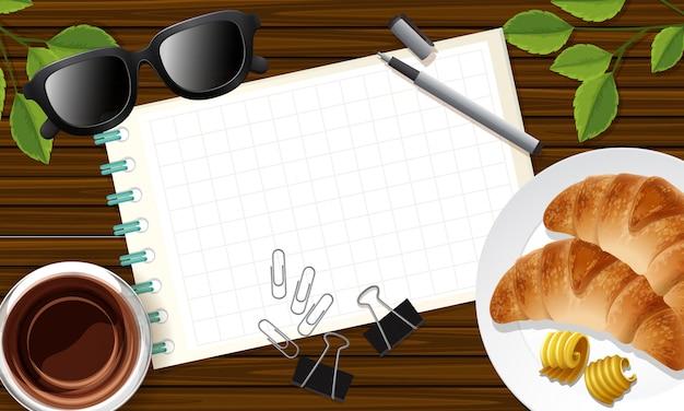 Nota em branco fechada no fundo da mesa com alguns adereços de folhas