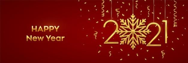 Números metálicos dourados pendurados 2021 com um floco de neve brilhante e confetes no banner vermelho