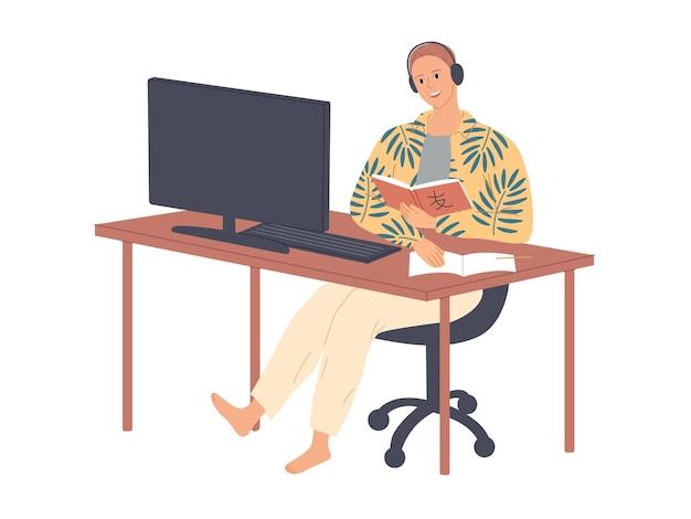 O aluno se senta à mesa com fones de ouvido e estuda