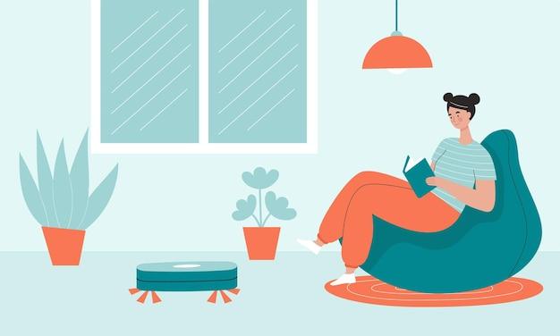 O aspirador robô limpa a sala enquanto a mulher lê um livro e descansa.
