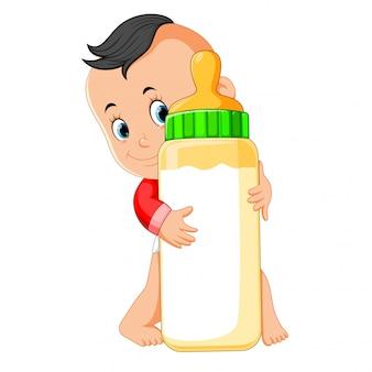 O bebê feliz jogando e abraçar a garrafa de leite