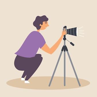 O cara meio sentado tira uma foto usando uma câmera slr em um tripé em um ambiente natural