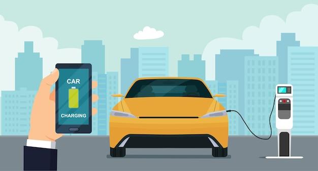 O carro elétrico está carregando, o dono do carro controla o processo por meio de um smartphone.