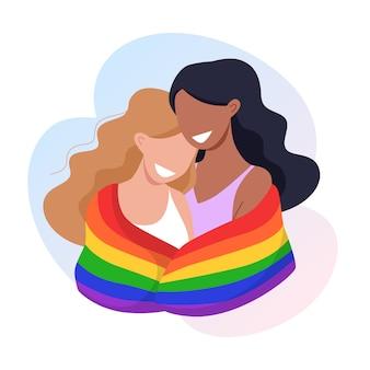O casal de jovens mulheres se abraça e segura uma bandeira do orgulho lgbt do arco-íris.