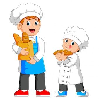 O chef está segurando um saco de pão com o menino ao lado dele