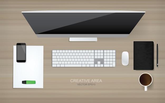 O computador da vista superior com objeto do escritório ajustou-se no fundo de madeira.