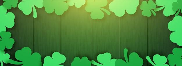 O design da bandeira feliz do dia de são patrício com folhas brilhantes de trevo em fundo de madeira.