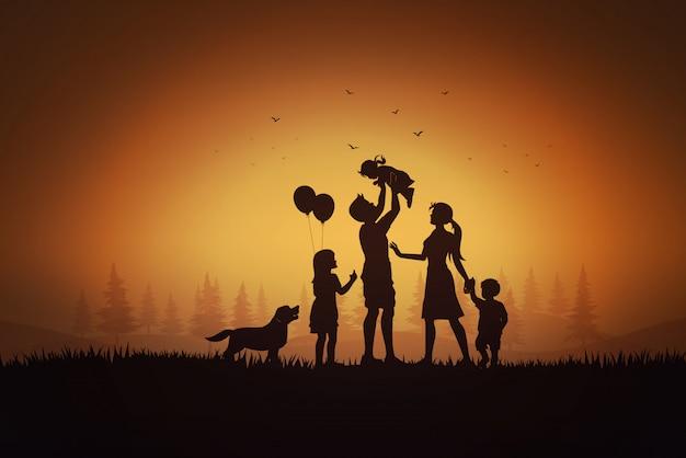 O dia da família feliz, a mãe do pai e as crianças mostram em silhueta o jogo na grama no por do sol.